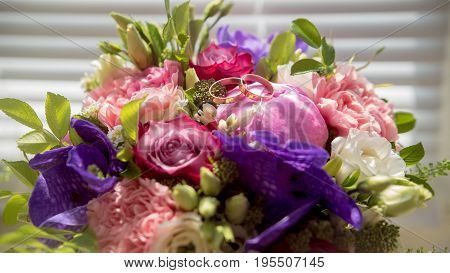 Wedding bouquet with golden rings, macro, horizontal view