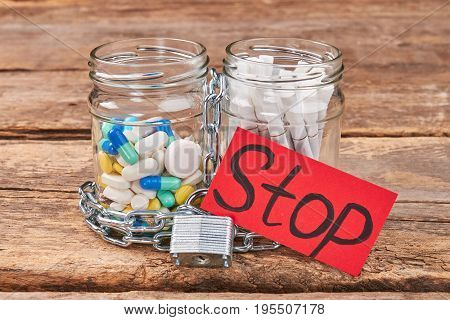 Cigarettes and pills, paper message. Jars with pills and cigarettes, metallic chain, padlock, message stop, wooden background. Stop harmful habits concept.