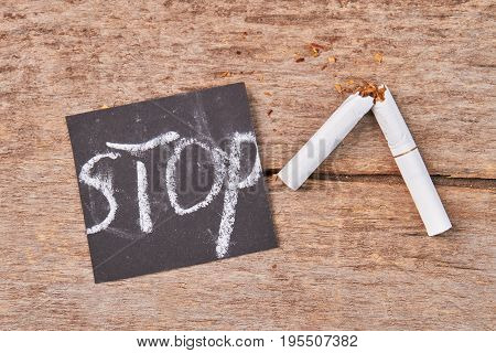 White cigarette with filter broken. Message stop, broken cigarette, wooden background. Stop smoking tobacco cigarettes.