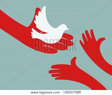 Close up of hand holding white dove and hands of children on pale green background