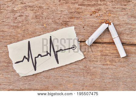 White tobacco cigarette broken. Broken tobacco cigarette, image of heartbeat, wooden background.