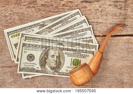 American money, wooden pipe for smoking. Dollar banknotes, wooden pipe, vintage wooden background.
