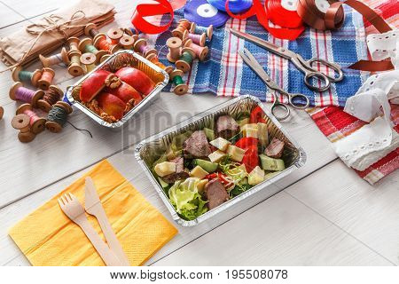 Lunch box healthy food delivery for dressmaker. Flat lay shot of foil container with diet meal for fashion designer at workplace. Diet nutrition, meat and vegetables