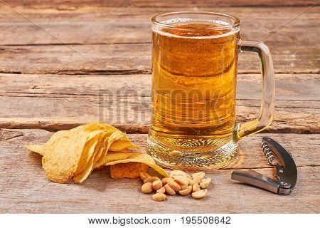 Glass of beer, chips, nuts, corkscrew. Concept of beer addiction.