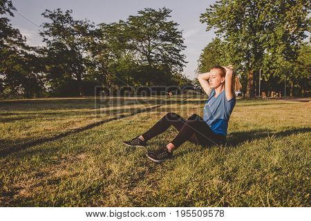 Relaxing Outdoor. Young Woman Sitting In The Park And Relaxing After Running
