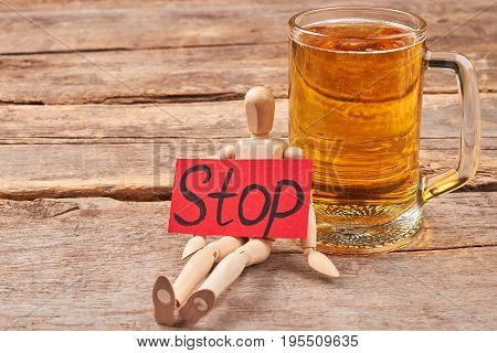 Beer addiction how to stop. Human wooden dummy, message stop, glass of beer, old wooden background.