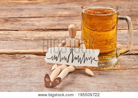 Abuse of beer leads to heart disease. Heartbeat image, human wooden dummy, mug with beer, wooden background.