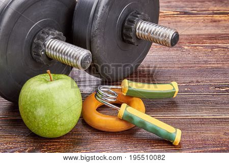 Healthy lifystyle concept. Dumbbells, green apple, expanders, wooden background.
