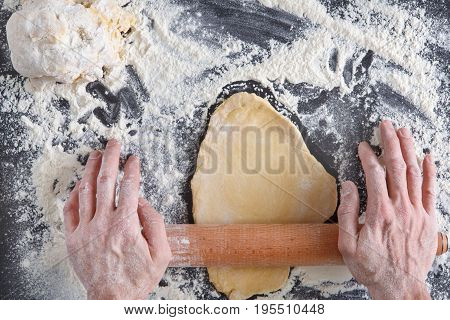 Baking concept. Hands top view roll dough on black background. Male baker