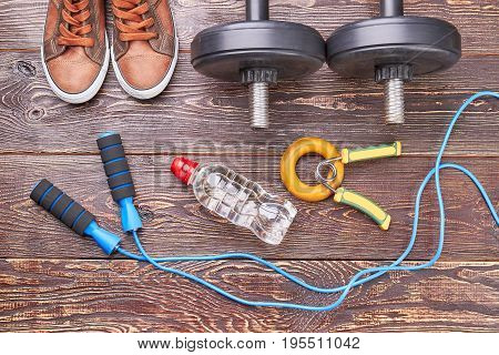 Get fit with gym training. Shoes, dumbbells, jump rope, bottle, expanders on wooden background.