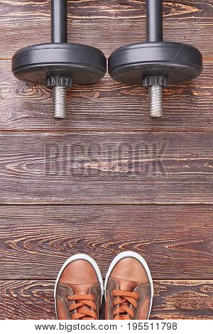 Dumbbells, sneakers, copy space. Metal weight object for lifting, shoes, wooden background.