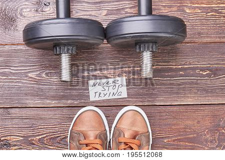 Weight lifting sport objects, shoes. Dumbbells and sneakers of sportsman in gym.