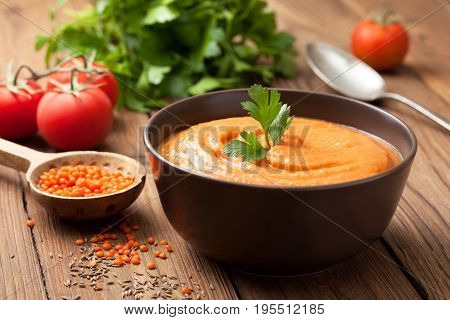 Soup puree of red lentils in a brown bowl fresh tomatoes parsley on an old wooden background