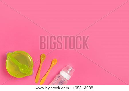 Green plate, a bottle, knife and spoon on pink table. Children dinner time. Top view. Copy space. Flat lay. Still life