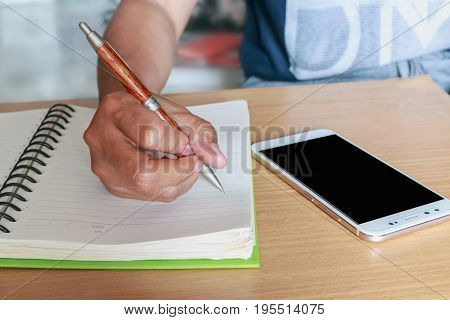 Hand holding a pencil writing on a notebook
