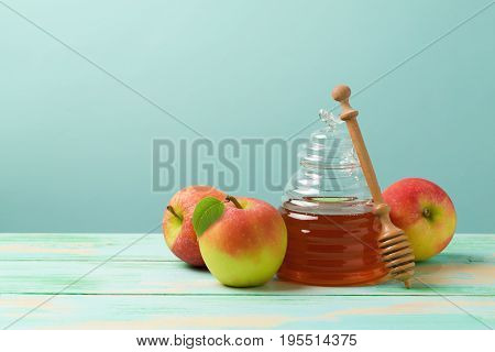 Rosh hashanah jewish new year holiday celebration concept. Honey and apples over blue background