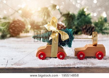 Christmas tree on toy car over festive background. Christmas holiday celebration concept