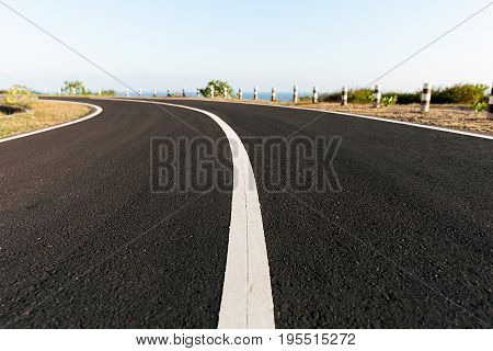 New Asphalt coastal road with white markings going round cliff edge bend, with blue sea and clear sky back drop.