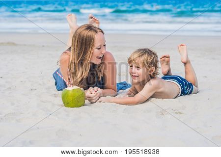 Mom And Son Enjoy The Beach And Drink Coconut