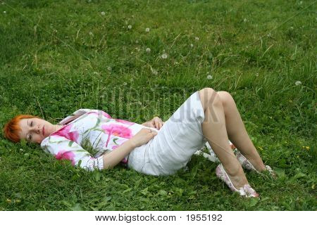 Sad Red-Haired Girl On A Grass