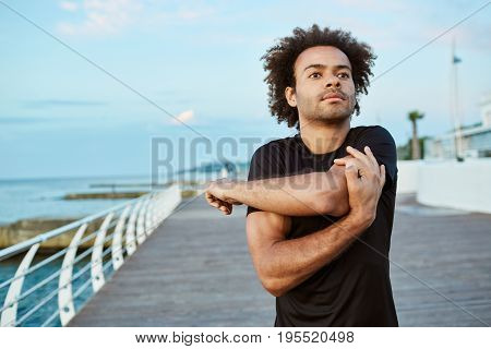 Sports, fitness and healthy lifestyle. Fit young Afro American man doing warm-up before running on the boardwalk in the morning.