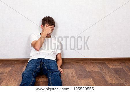 Sad Young Man on the Floor in the Room