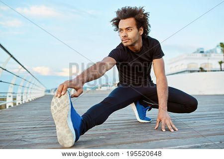 Dark-skinned male athlete with bushy hair doing exercise and stretching legs. Enjoying sport and sunrise. Wearing black sport clothing and blue sneakers.