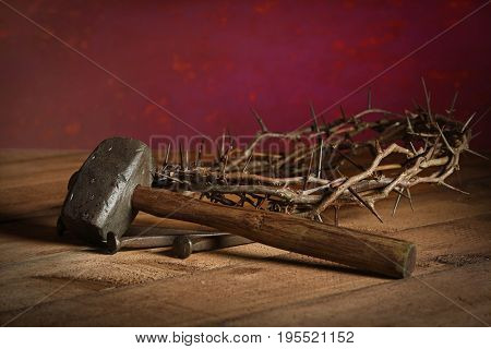 Mallet, crown of thorns and large nails on wooden table over red background