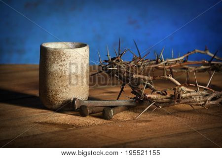 Communion cup with crown of thorns and nails over wooden table over blue background