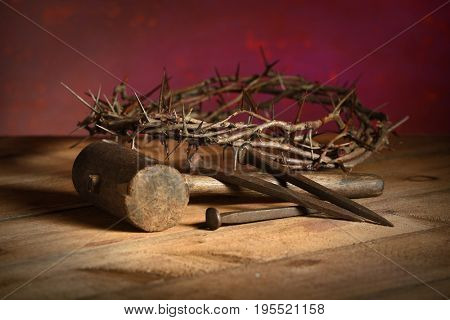 Crown of thorns, mallet and nails over vintage table over red background