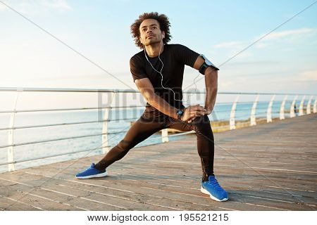 Dark-skinned male runner with beautiful fit body warming-up before cardio workout. Male athlete in sportswear stretching legs with lunge hamstring stretch exercise by the sea in morning sunlight.