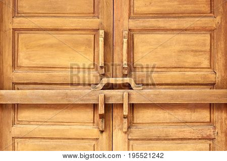 Closed wooden door with ancient locking bar Traditional wooden door latch