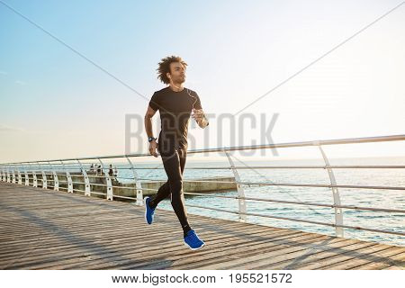 Attractive male athlete wearing stylish black sport clothing and blue sneakers. Figure of man athlete doing cardio running exercises on sunny summer morning. People, sports, fitness and health concept.