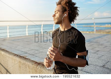 Portrait of Afro-American runner with closed eyes after cardio training wearing black T-shirt with earphones and bottle of mineral water in hands. Relaxing after jogging by the sea.