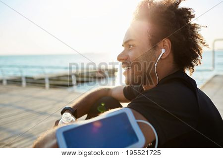 Portrait of smiling young African-American sportsman with earphones on in black T-shirt. Resting on a wooden pier after successful jogging. Doing exercises by the sea.