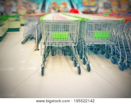 Blurred empty shopping carts (green and white handles) in a large supermarket; park attached to one another on cart corrals; ready for customers to use. Perspective view and bottom copy space for text.