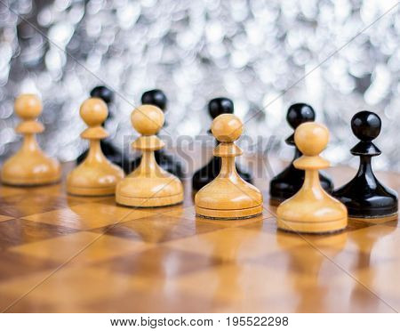 White and black pawns on chessboard with bokeh