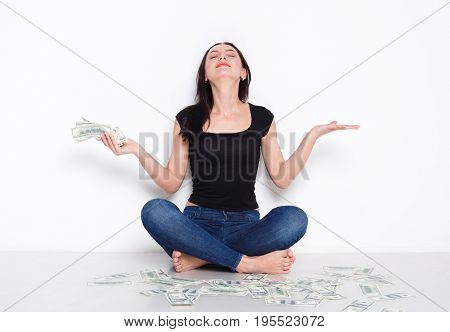 Excited woman sitting with lot of money on floor and smile. Happy girl with american dollar banknotes - lottery jackpot and financial success concept