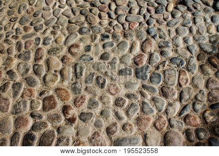 Round stones in the ground. Texture of the cobblestones in Park. The paving stones. Background