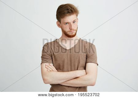 Portrait of young brutal man with beard looking at camera with crossed arms over white background. Copy space.