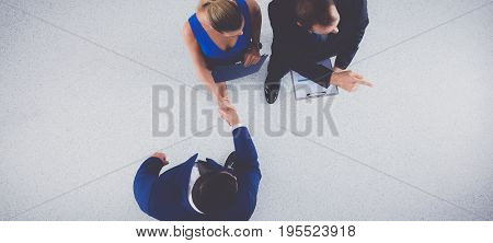 Young business people shaking hands - standing topview .