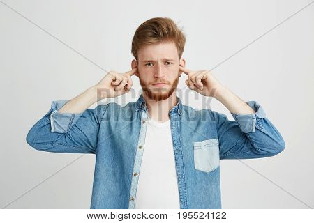 Displeased young handsome man with beard frowning closing ears over white background. Copy space.