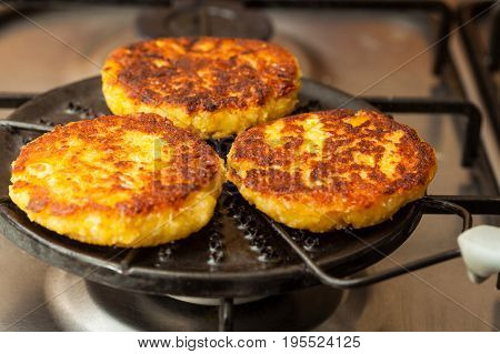 Traditional Colombian Arepa de Choclo Preparation : Corn breads being roasted on a round grill