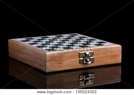 Chessboard on a black background. Folding chess in a wooden case.