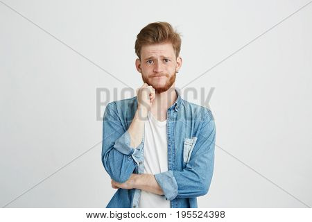 Portrait of sad upset young guy looking at camera with hand on chin over white background. Copy space.