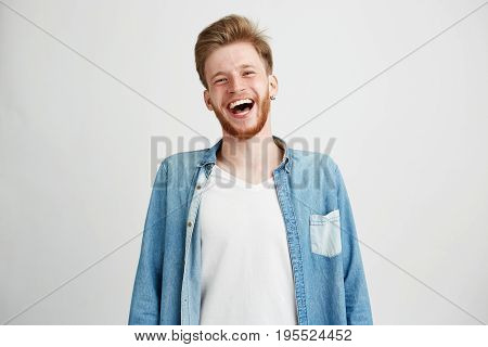 Portrait of young handsome hipster man with beard smiling laughing looking at camera over white background. Copy space.