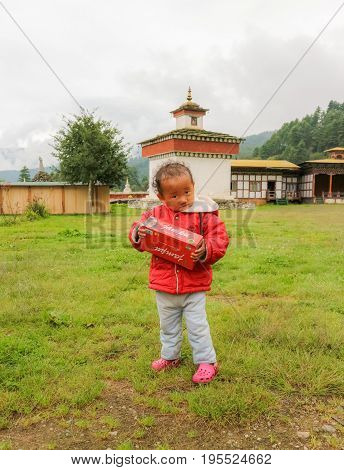 Bumthang Bhutan - September 13 2016: Sweet little Bhutanse girl holding a red box in her hands near Kurjey Lhakhang (The Temple of Imprints) Bumthang Bhutan South Asia
