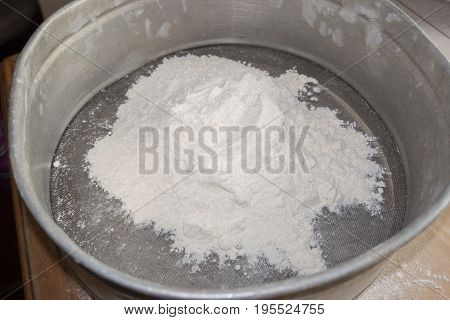 White flour in a sieve. Top view