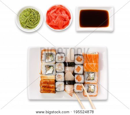 Japanese food restaurant. Sushi set served on white platter with soy sauce, ginger, wasabi and chopsticks picking one piece. Top view, flat lay at white background with copy space