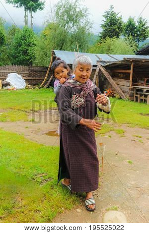 Bumthang Bhutan - September 13 2016: Old Bhutanese woman with a child in a village in Bumthang valley Bhutan.